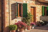 Beautiful stone house with windows, green shutters and flowers. Pienza, Italy.