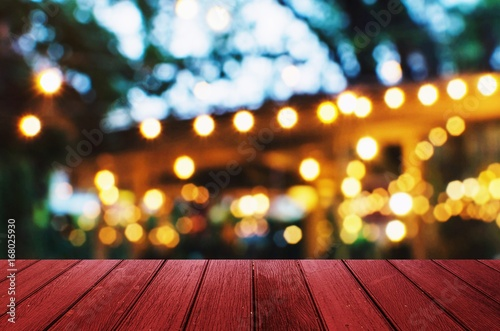 empty red wooden floor or wooden terrace with abstract night light bokeh of night festival in garden, blurred background, copy space for display of product or object presentation, vintage color tone - 168025930