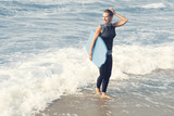 blond woman in wetsuit walking out of the water