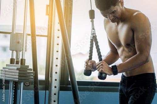 Sticker muscular man hard exercise with cable weight machine in gym.