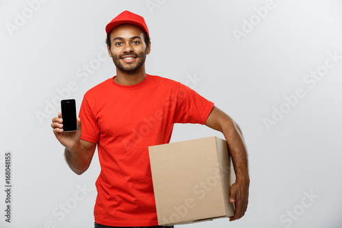 Delivery Concept - Portrait of Handsome African American delivery man or courier with box showing mobile phone on you to check the order Poster
