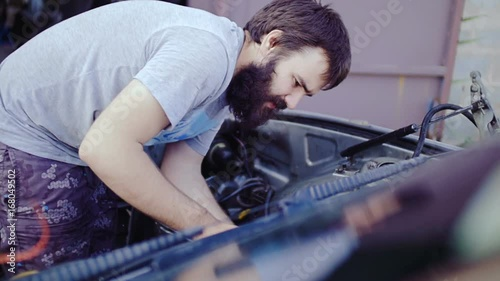 The auto mechanic is repairing the car.