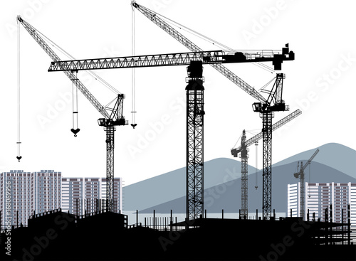 industrial cranes and house building near mountains