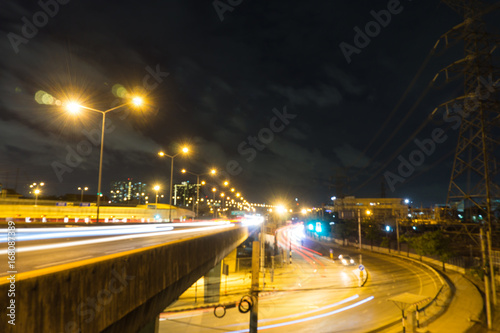 motion blurred and light trail of car on and under the rama 7 bridge with dark sky and cloud