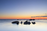 Several rocks in quiet sea at sunset