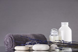 Spa. The towel is rolled up, white pebbles, two bottles of cream. Lavender. The background is gray.