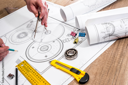 engineer measures the dimensions of the drawing.