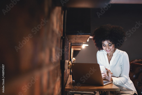 African woman looking at smartphone while working in office