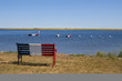 Bench and boats with French Acadian flag in Bouctouche, New Brunswick