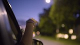 Young Woman Puts Her Hand Out Car Window To Feel The Breeze, At Night, On Tree Lined Street In City - 168127559