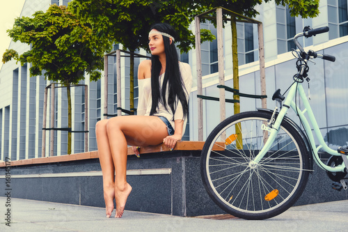 Wall mural Female sits on a bench over modern building background after bicycle ride.