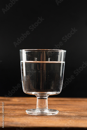 A glass of clean water on an old wooden background