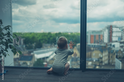 Little baby sitting on balcony in the city - 168159111