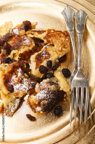Wall mural kaiserschmarrn with raisins and powdered sugar on a gold colored plate