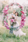 Newlyweds are holding the bouquet of peonies and standing behind the wedding peonies arch in the sunny spring field. Close-up vertical photo. - 168161775