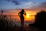 Beautiful woman silhouette at the ocean coast over sunset sky