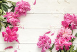 Pink peonies on white wooden background. Place for the text.