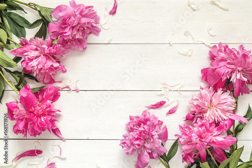 Wall mural Pink peonies on white wooden background. Place for the text.
