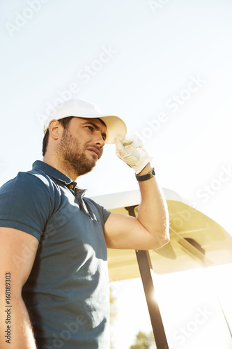 Young male golfer in hat
