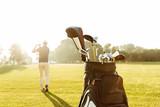 Back view of a male golfer swinging golf club