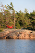 Relaxing in a red hammock strung between the pine trees on an island. Camping in the Canadian wilderness.