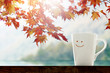 Happiness and Relaxation moment in Fall Season Concept, Happy smiley face Coffee Cup with Autumn Foliage Maple Leaf, Blurred Lake and Mountain  as background