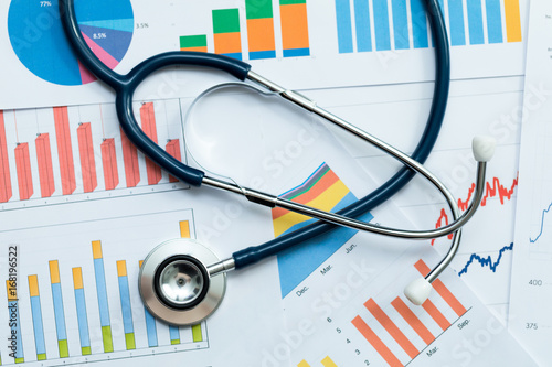 stethoscope on healthcare stats and financial analysis charts