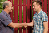 two farmers shaking hands and takling to each other - 168197384