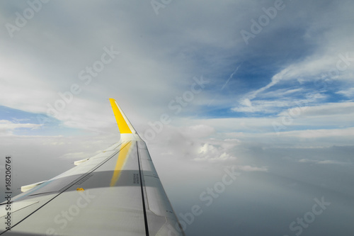Aircraft wing flying over a blue cloudscape