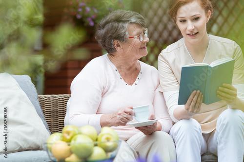 Poster Nurse reading to pensioner