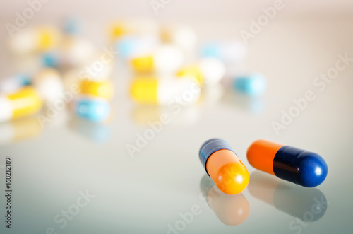 Fotobehang Apotheek Pharmacy theme. Orange, Yellow, Blue, White Isolated Capsules on the White Surface. Closeup