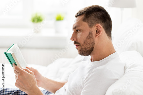 man reading book in bed at home Poster
