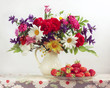 Bouquet of garden flowers in a jug and strawberries.