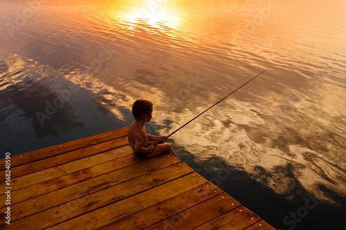 Chłopiec jest usytuowanym na drewnianym doku i połowie przy zmierzchem.