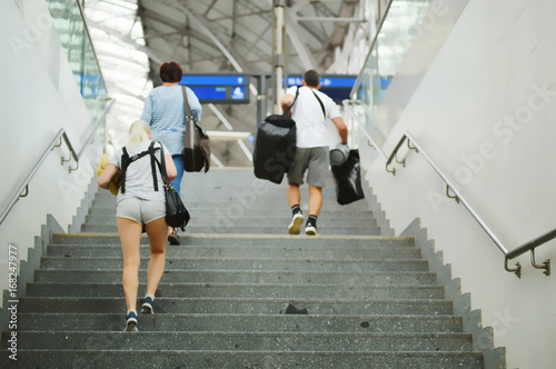 People going to the stairs at the station, blurred