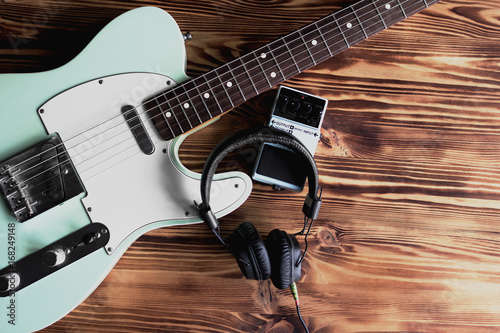 Electric guitar, pedal and headphones on the wooden table. Making music and sound recording concept. - 168249148