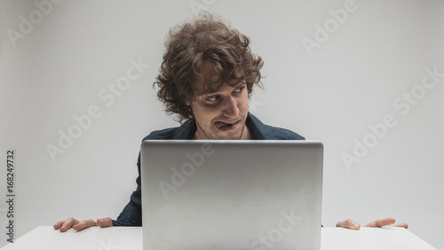 aroused man with tongue stuck out watching porn - 168249732