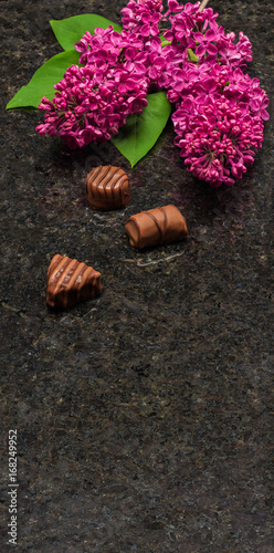 Lilac blossom branches and chocolates on Antique Brown granite countertop