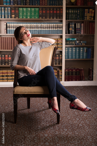 Plakát Young caucasian woman dressed like Jackie Kennedy poses in a library