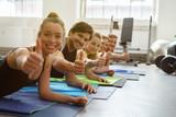 Fototapety gruppe im fitness-studio zeigt daumen hoch