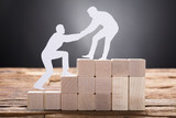 Businessman Pulling Colleague While Standing On Wooden Blocks - 168279798