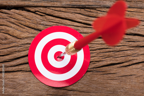 Red Arrow In Dartboard On Table
