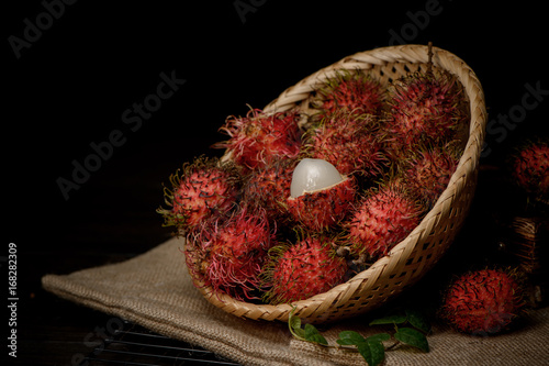 rambutan in a bamboo basket on wooden table isolated on 