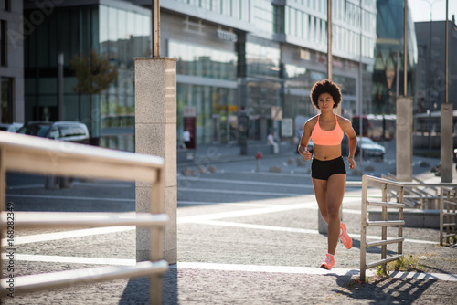 Active young sports woman running outdoors on a sunny day