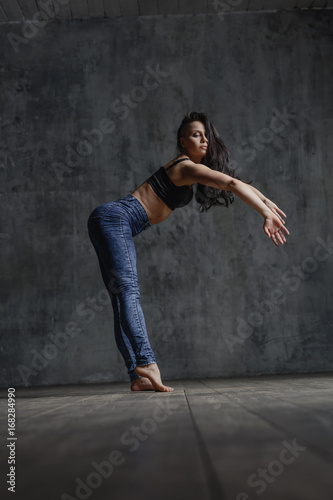 Young beautiful dancer is posing in studio