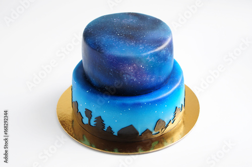 Artistic two-tiered cake with the image of the cosmos drawn by airbrush. Galaxy, stars in the night sky and silhouettes of trees. Cutout. Picture for a menu or a confectionery catalog. - 168292344
