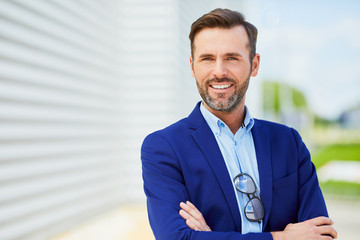 Portrait of handsome confident middle-aged business executive looking at camera smiling with arms crossed outside