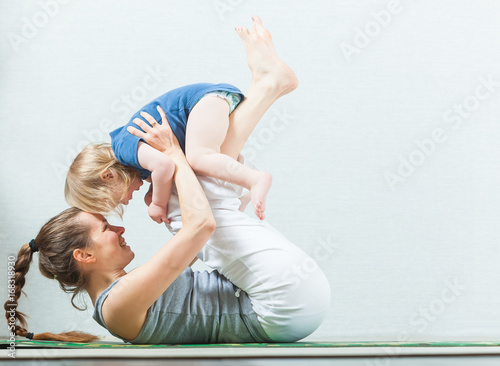 Wall mural Mom and child are practicing yoga at home
