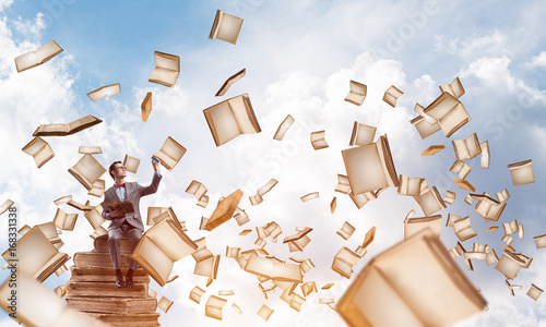 Young businessman or student studying the science and books fly around