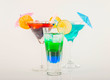 Colorful cocktail decorated with fruit, colorful umbrella, ice cubes, party night